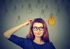 Mujer en los vidrios que miran para arriba el bulbo ligero de la idea sobre la cabeza Imagenes de archivo