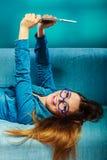 Mujer en los vidrios que ponen en el sofá con la tableta de la PC Fotos de archivo libres de regalías