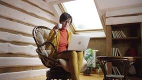 Mujer en los vidrios que practican surf Internet en el ordenador portátil y que beben el café en ático almacen de metraje de vídeo