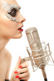 Mujer en máscara de la hoja con el micrófono Imágenes de archivo libres de regalías
