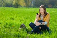 Mujer en móvil en el parque Fotografía de archivo libre de regalías