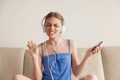 Mujer en música que escucha de los auriculares del teléfono móvil Fotos de archivo