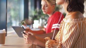 Mujer en música que escucha de los auriculares en smartphone metrajes