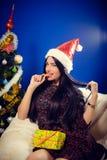 Mujer en mandarín penetrante del sombrero de Papá Noel por otra parte Imágenes de archivo libres de regalías