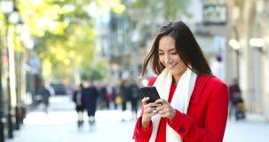 Mujer en mandar un SMS rojo en el teléfono en invierno