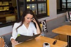 Mujer en menú de la lectura del café Imagenes de archivo