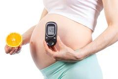 Mujer en metro embarazada de la glucosa que se sostiene y anaranjado, diabetes y la nutrición sana durante embarazo Fotografía de archivo libre de regalías