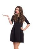 Mujer en Mini Dress Presenting Something negro Fotografía de archivo libre de regalías