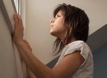 Mujer en mirar fijamente hacia fuera ventana Imágenes de archivo libres de regalías