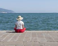Mujer en muelle en sol del verano Foto de archivo