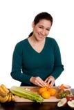 Mujer en naranja de la peladura de la cocina Imagenes de archivo