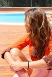 Mujer en naranja por la piscina Imagen de archivo