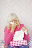 Mujer en nariz que sopla de la cama Fotografía de archivo
