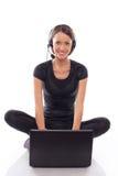 mujer en neadphones con la computadora portátil en un blanco Imágenes de archivo libres de regalías