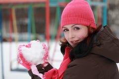 Mujer en nieve rosada del mantiene del sombrero en invierno foto de archivo libre de regalías