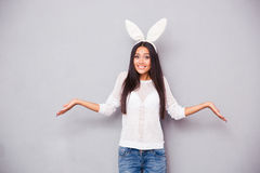 Mujer en oídos de conejo que encoge sus hombros Imagen de archivo