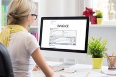 Mujer en oficina con el documento de la factura de la muestra en el ordenador fotografía de archivo