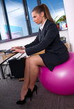 Mujer en oficina en bola de los pilates fotografía de archivo