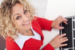 Mujer en oficina que pulsa en el teclado - sonriendo Fotografía de archivo