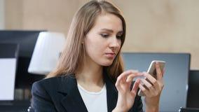Mujer en oficina usando Smartphone, en línea hojeando almacen de video