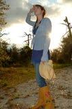 Mujer en país con el sol de configuración Fotos de archivo