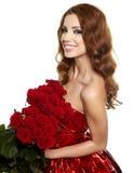 Mujer en pañería roja con las rosas rojas Foto de archivo