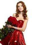 Mujer en pañería roja con las rosas rojas Imagenes de archivo