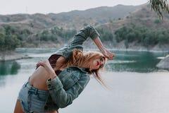 Mujer en pantalones cortos y chaqueta que presenta en naturaleza con un lago en el fondo imágenes de archivo libres de regalías