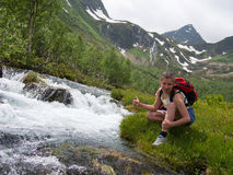 Mujer en pantalones cortos y con la mochila que se sienta en el banco de The Creek y de la sonrisa Imágenes de archivo libres de regalías