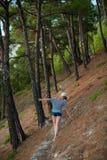 Mujer en pantalones cortos y sombrero que caminan el bosque del verano Imagen de archivo libre de regalías