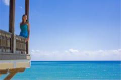 Mujer en paraíso en un balcón Imagenes de archivo