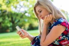 Mujer en parque con el teléfono elegante Imagen de archivo libre de regalías