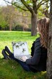 Mujer en parque con la computadora portátil Imágenes de archivo libres de regalías