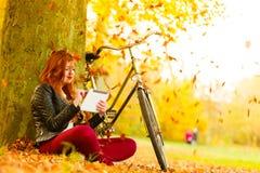 Mujer en parque del otoño usando la lectura de la tableta imagen de archivo libre de regalías