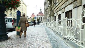 Mujer en paseo negro de la capa con el perro en la calle de Praga almacen de video