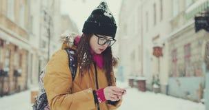 Mujer en paseos de moda del equipo en la ciudad del invierno que pasa por los cafés locales, textos vía su teléfono, hojeando Int metrajes