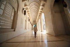 Mujer en pasillo dentro de la mezquita magnífica en Omán Imagen de archivo libre de regalías
