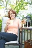 Mujer en patio trasero con café y galletas Fotos de archivo