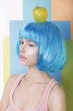 Mujer en peluca azul con Apple en su cabeza Imagenes de archivo