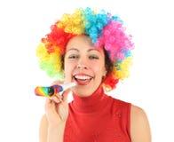 Mujer en peluca del payaso y con el ventilador del partido, riendo Fotografía de archivo libre de regalías