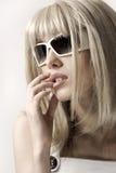Mujer en peluca y gafas de sol rubias foto de archivo