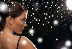 Mujer en pendientes del diamante del vestido de noche que llevan Imagenes de archivo