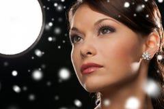 Mujer en pendientes del diamante del vestido de noche que llevan Imagen de archivo libre de regalías