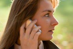 Mujer en perfil en el teléfono celular Imagen de archivo