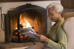 Mujer en periódico de la lectura de la sala de estar fotos de archivo libres de regalías
