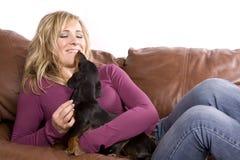 Mujer en perro negro del wth del sofá Fotografía de archivo