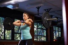 Mujer en pesos de elevación del gimnasio Imagenes de archivo