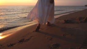 Mujer en pie desnudo de los sundress blancos que camina en la playa del verano pierna ascendente cercana de la mujer joven que ca metrajes