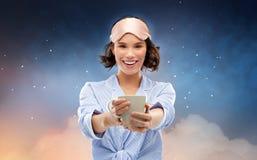 Mujer en pijama y caf? de consumici?n de la m?scara el dormir foto de archivo libre de regalías