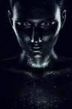 Mujer en pintura negra con las chispas en oscuridad Fotografía de archivo libre de regalías
